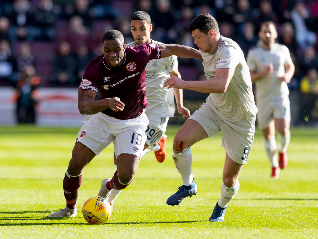 30th March 2019, Tynecastle Park, Edinburgh, Scotland; Ladbrokes Premiership football, Heart of Midlothian versus Aberdeen; Scott McKenna of Aberdeen and Uche Ikpeazu of Hearts compete for possession of the ball