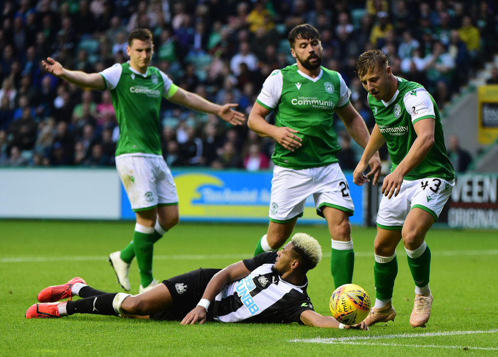 EDINBURGH, SCOTLAND - JULY 30: Joelinton of Newcastle is challenged by Paul Hanlon, Darren McGregor and Sean Mackie of Hibernian during the Pre-Season Friendly match between Hibernian FC and Newcastle United FC at Easter Road on July 30, 2019 in Edinburgh, Scotland.
